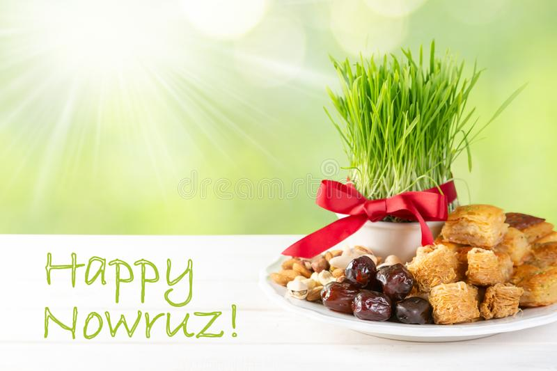 Nowruz holiday concept - grass, baklava sweets, nuts and seeds stock photography