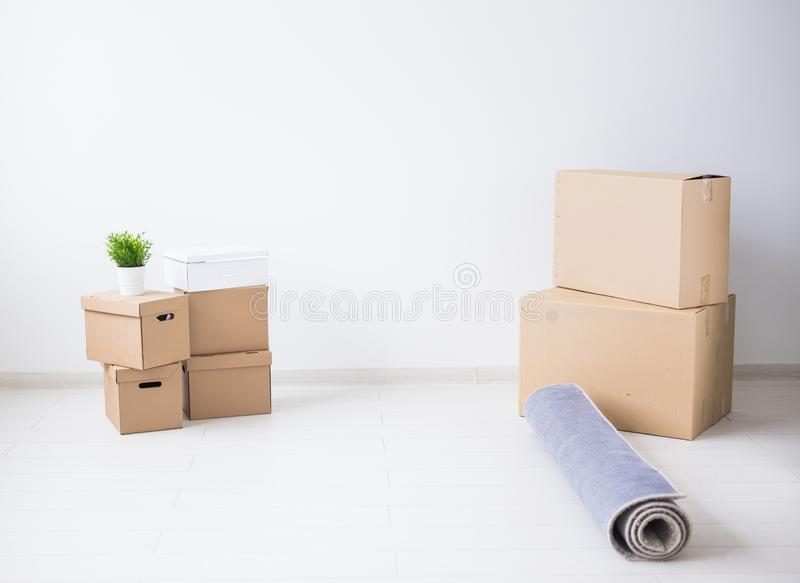 Nowy domu, chodzenia i przeniesienia pojęcie, - kartony i biel puszkują z zieloną rośliną na białego pokoju tle z zdjęcie royalty free