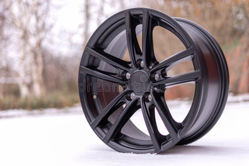 Nowy elegancki czarny oczyszczony aluminiowego aliażu koło na białym śniegu, Zima z bliska obrazy stock