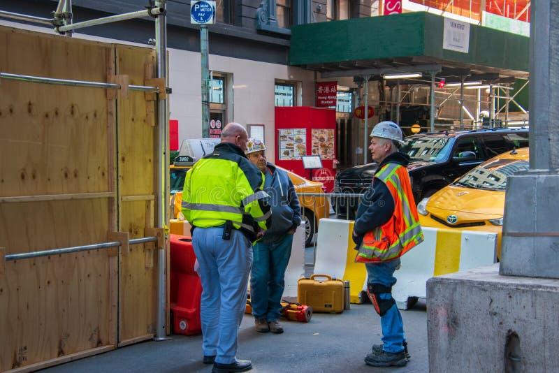 Nowy Jork, NY - Kwiecień 3, 2019: Grupa trzy pracownika budowlanego w odbijających kamizelkach i ciężkich kapeluszach przy budową zdjęcie royalty free