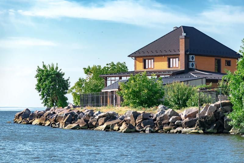 Nowy nowożytny cegła dom, chałupa na brzeg Kakhovsky rezerwuar w Kherson regionie Ukraina przeciw niebieskiemu niebu lub obrazy royalty free
