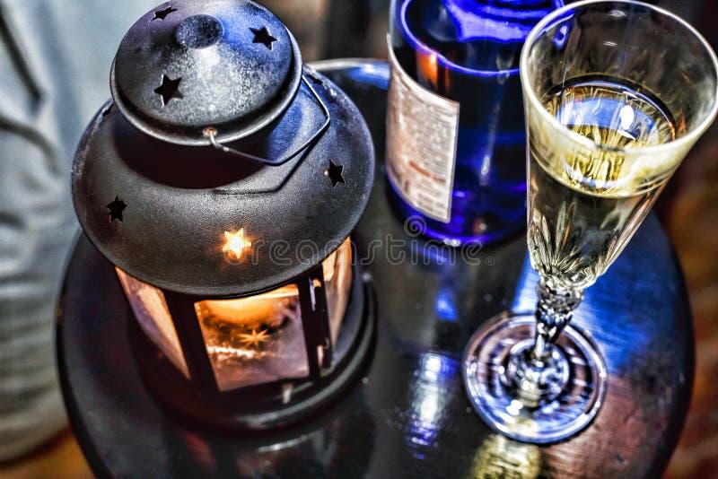 Nowy Rok boże narodzenia Szampan w szkłach w butelce i, Bożenarodzeniowy lampion z płonącą świeczką na świątecznym stole obraz royalty free