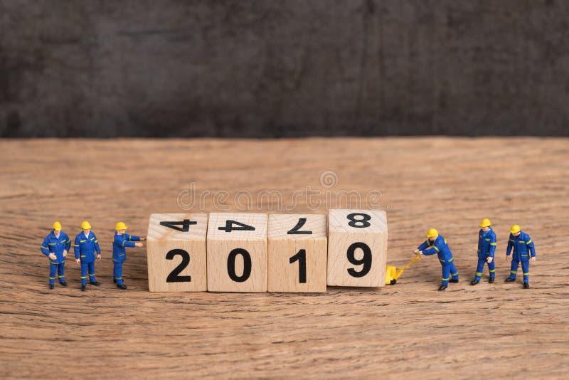 Nowy rok 2019 jest nadchodzącym pojęciem, śliczni miniaturowi ludzie jednolitego pracowników personel kona buduje sześcianu drewn zdjęcia royalty free