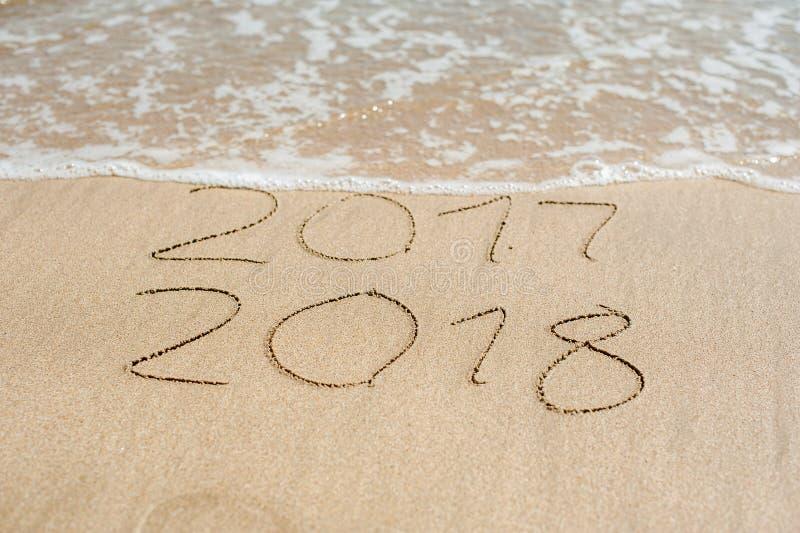 Nowy Rok 2018 jest nadchodzącym pojęciem - inskrypcja 2017, 2018 na plażowym piasku i fala prawie zakrywa cyfry 2017 fotografia stock