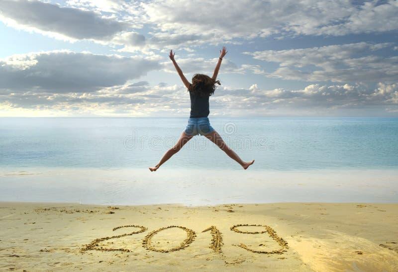 Nowy Rok 2019 na piasku, szczęśliwa dziewczyna z rękami w górę doskakiwania na plaży zdjęcie stock
