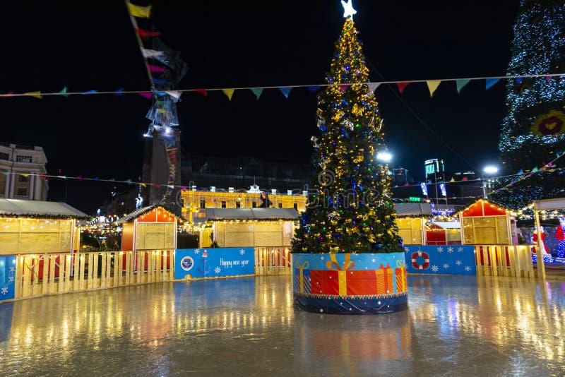 Nowy rok nocy scena świąteczna choinka z dekoracjami na lodowisku na tle Bożenarodzeniowa iluminacja sk i noc zdjęcie stock