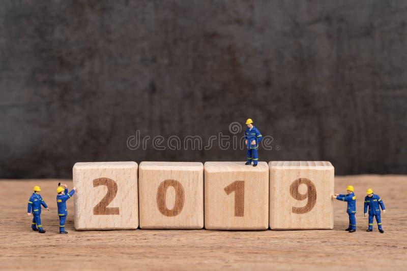 Nowy rok 2019 zaczyna pojęcie, śliczni miniaturowi ludzie pracowników personel kona buduje sześcianu drewnianego blok jako rok li zdjęcie stock