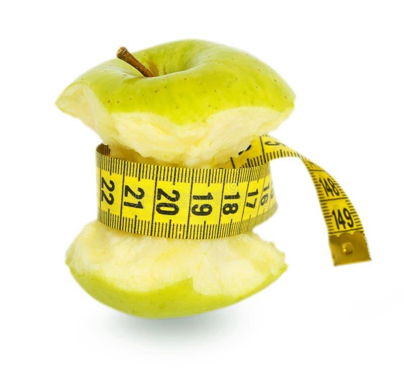 Noyau vert de pomme et bande de mesure jaune photographie stock libre de droits