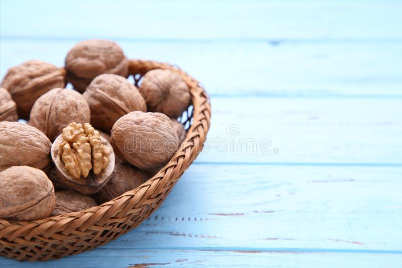 Noyaux de noix dans le panier sur le fond en bois bleu Nourriture saine de noix image libre de droits
