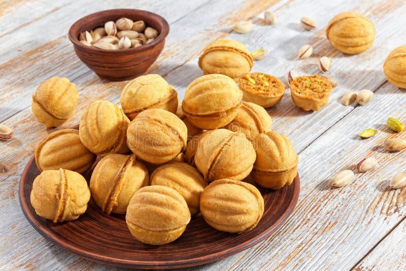 A noz deu forma às cookies do sanduíche do biscoito amanteigado enchidas com o cond doce imagem de stock