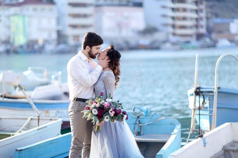 Nozze dello sposo e della sposa sul pilastro con le barche sul mare fotografia stock