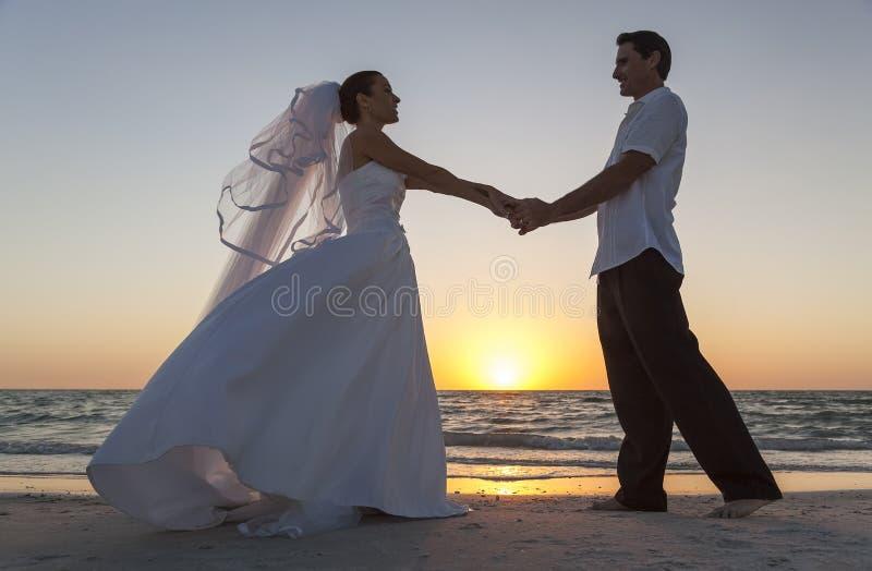 Nozze di spiaggia di Married Couple Sunset dello sposo e della sposa fotografia stock