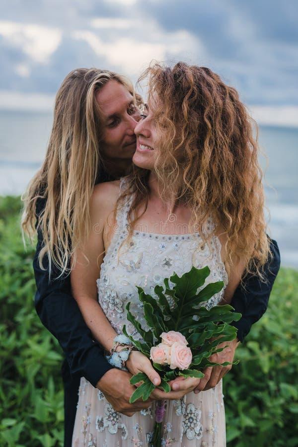Nozze lovestory, appena coppia sposata vicino all'oceano al tramonto fotografia stock libera da diritti