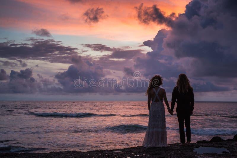 Nozze lovestory, appena coppia sposata vicino all'oceano al tramonto immagini stock libere da diritti