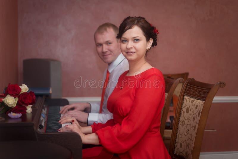 Nozze: persone appena sposate, sposa e sposo, coppie degli amanti, giocanti il piano fotografia stock