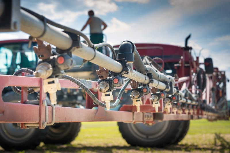 Nozzles on the spray bar, against the background of the sprayer and the person standing on the barrel, during refueling.  royalty free stock photos