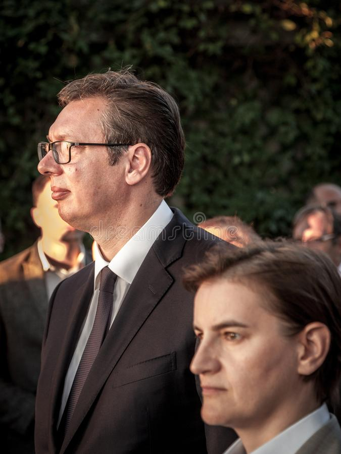 Aleksandar Vucic, President of Serbia standing and listening to a speech while Ana Brnabic, Prime Minister, is on foreground. NPicture of Aleksandar Vucic and royalty free stock images
