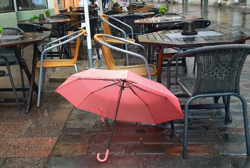 Pink Umbrella on Street cafe wet asphalt  coral  on wet rain drops evening  light   Rainy Autumn relax in Old Town empty ci. NPink Umbrella on Street wet asphalt stock images