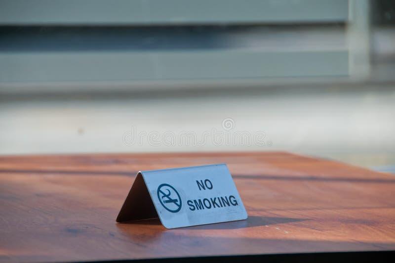 Nr - rokend metaalteken op houten lijst in koffie stock fotografie