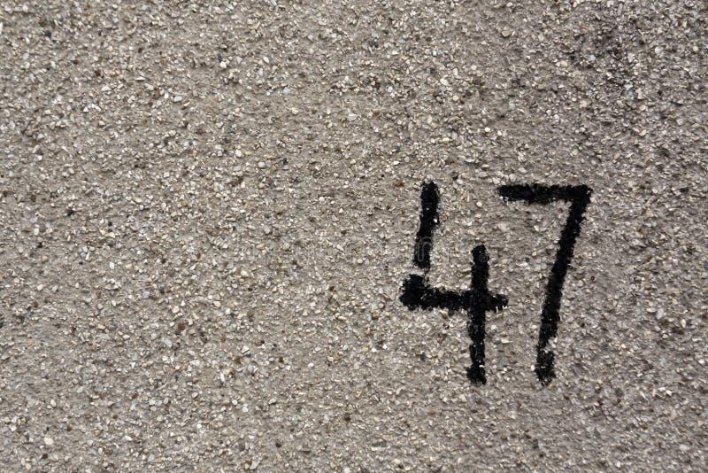 Nr. siebenundvierzig auf grauer Gipswand stockbilder