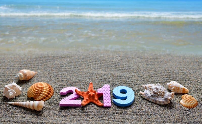 Nr. 2019 und Seeoberteil auf dem Sandstrand stockfoto