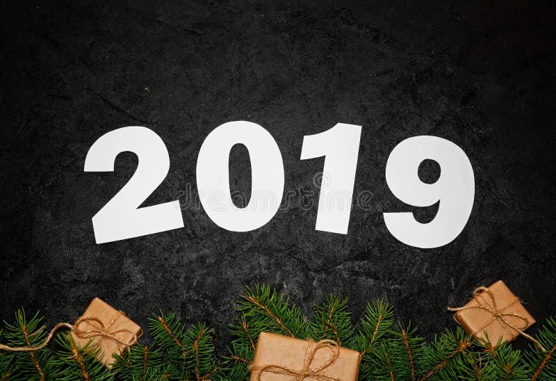 Nr. zwei tausend und neunzehn von den grünen Tannenzweigen mit kleinen Geschenkboxen auf dunklem Hintergrund Flache Lage lizenzfreies stockbild