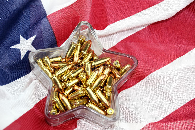 NRA candy dish. 9mm ammunition in star shaped glass candy dish resting on an American flag stock image