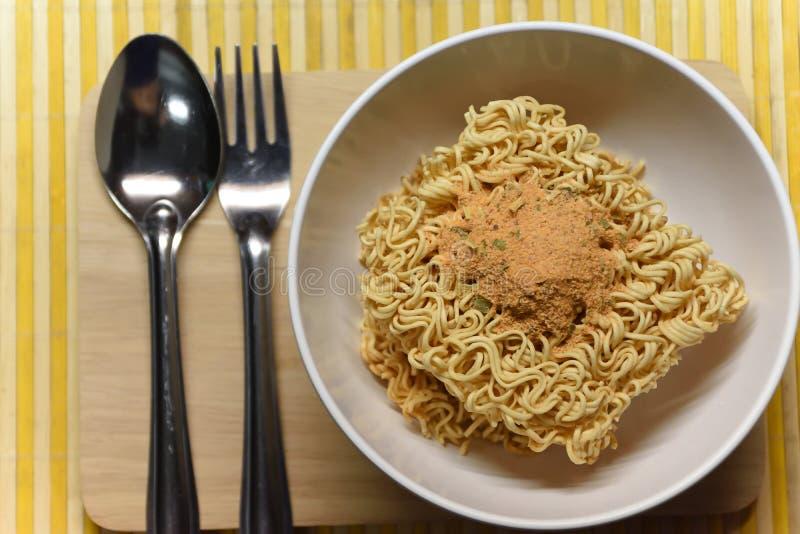 nstant nudlar smaksatte soppa i bunke med gaffeln arkivfoto