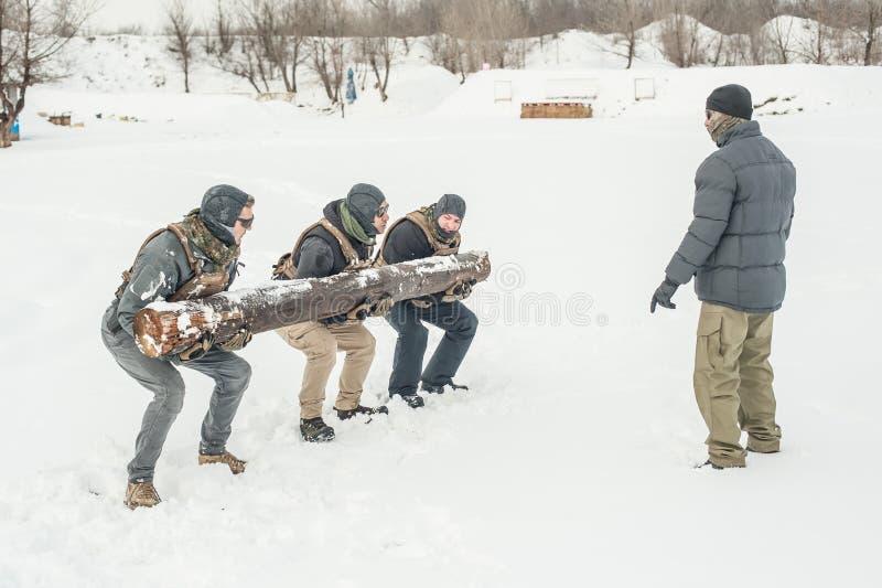 Nstructor und Armeesoldaten haben Training mit enormem Holzklotzholz lizenzfreie stockbilder