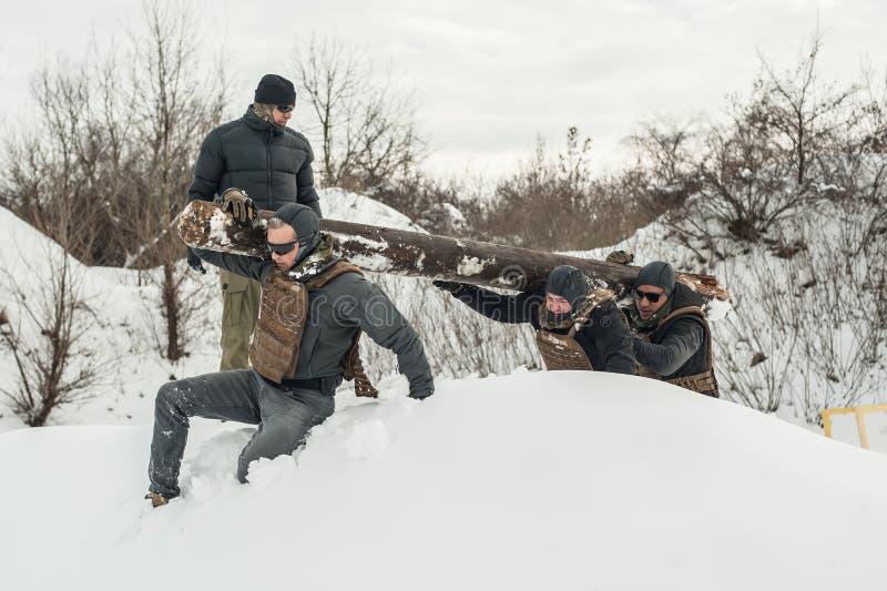 Nstructor und Armeesoldaten haben Training mit enormem Holzklotzholz stockfotografie