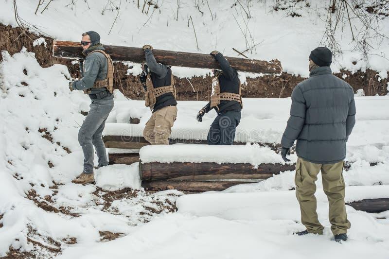 Nstructor und Armeesoldaten haben Training mit enormem Holzklotzholz lizenzfreie stockfotografie