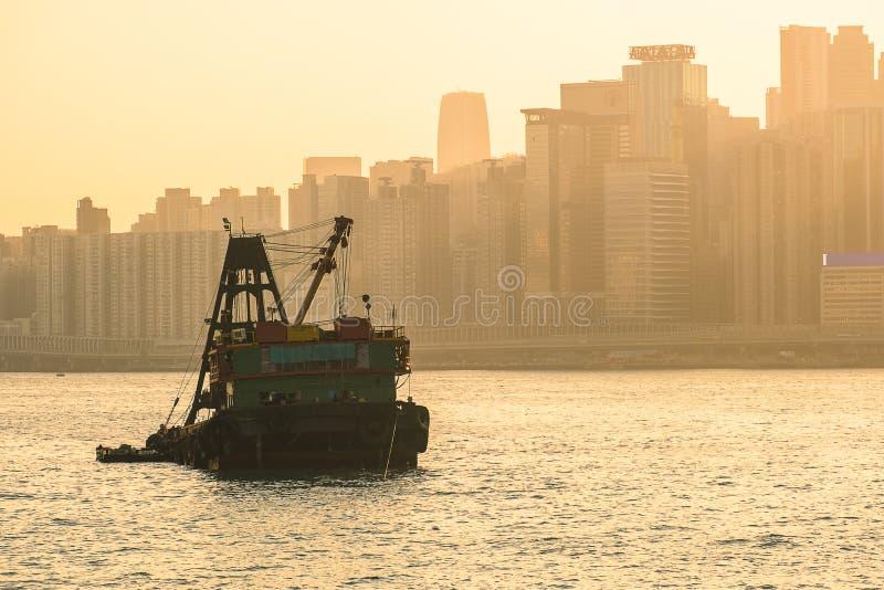 Nternational zbiornika ładunku statek w oceanie z Hong Kong pejzażu miejskiego tłem w ranku zmierzchu i wschód słońca niebie, obraz stock