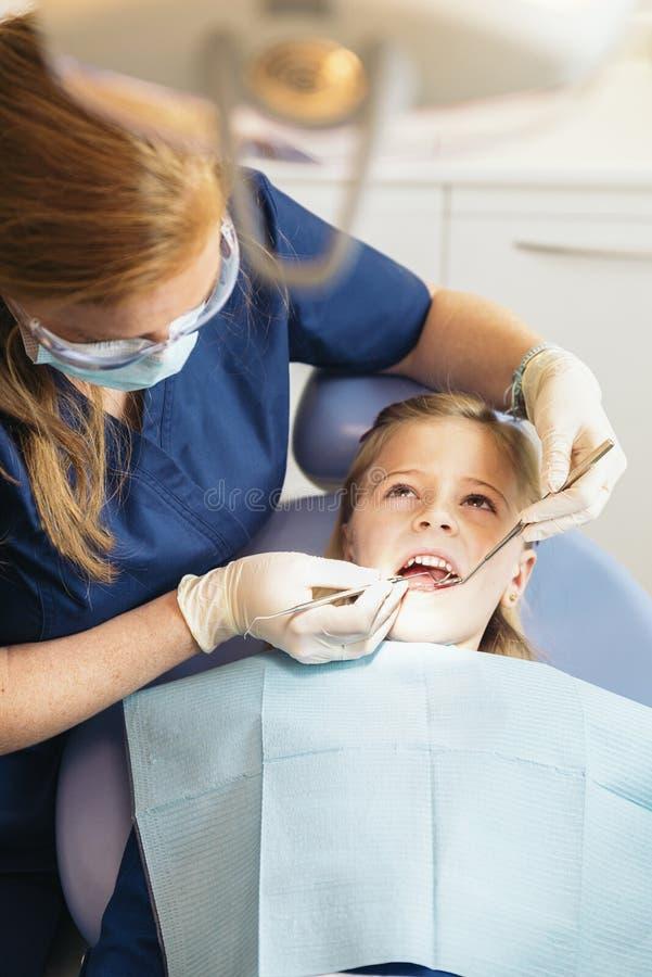 Ntists con un paziente durante l'intervento dentario alla ragazza immagine stock libera da diritti