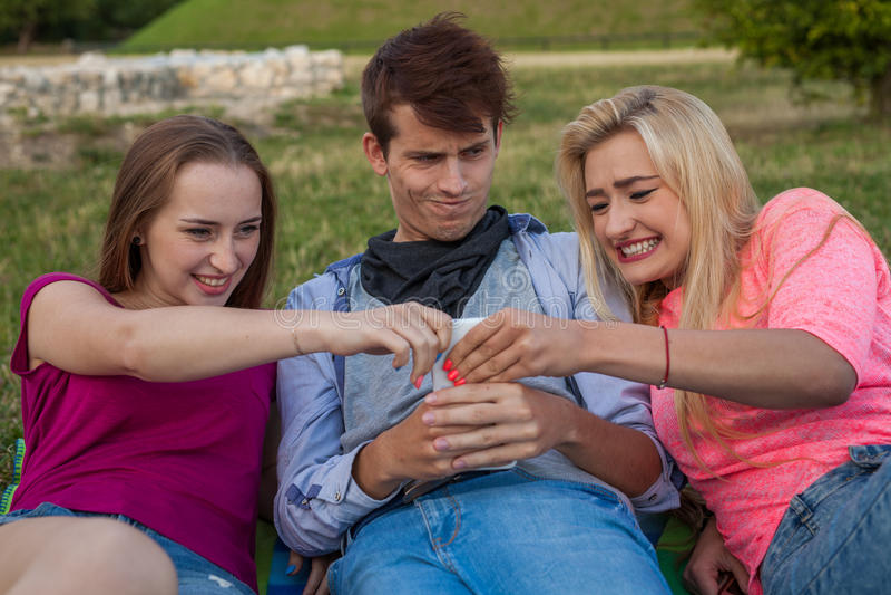 Nu mijn draai! Drie vrienden die voor een mobiele telefoon vechten stock fotografie