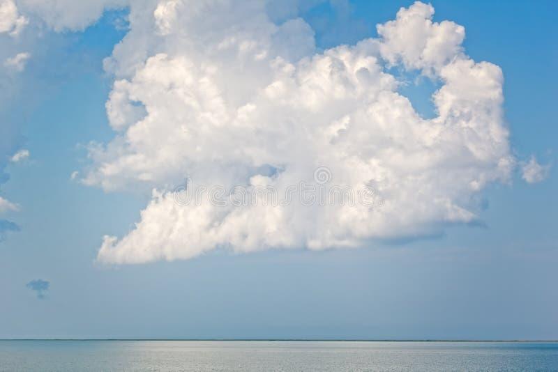 Nuage blanc au-dessus de la mer contre un ciel orageux photo stock