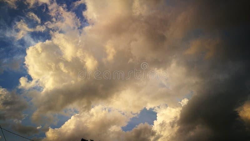Nuage blanc et une partie du nuage de pluie avec le fond de ciel bleu pendant le coucher du soleil photographie stock