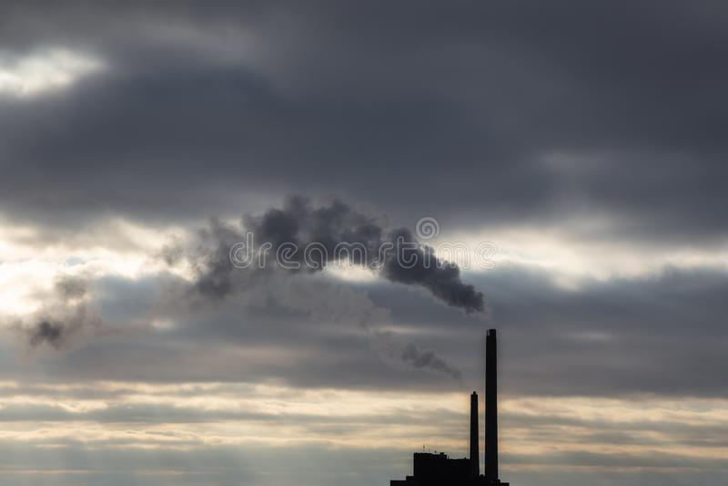 Nuage de fumée foncé lourd de cheminée industrielle dans le coucher du soleil avec l'espace de copie images stock