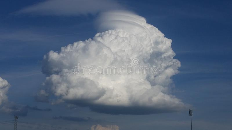 Nuage gonflé tourbillonné contre un ciel bleu profond photo libre de droits