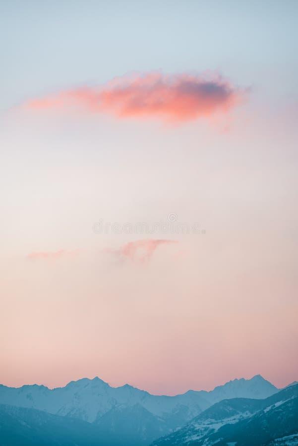 Nuage rouge au-dessus des montagnes éloignées photos stock