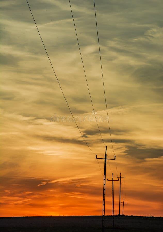 Nuages après coucher du soleil et poteaux électriques photographie stock libre de droits