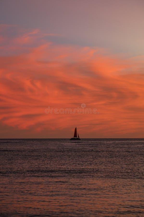 Nuages au coucher du soleil avec voilier image stock
