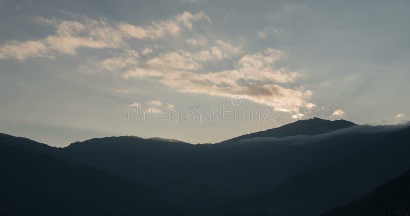 Nuages au coucher du soleil sur un fond des montagnes banque de vidéos