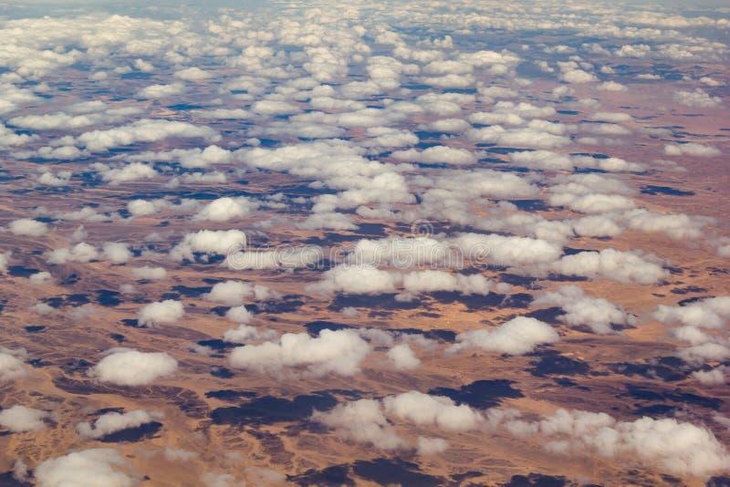 Nuages au-dessus d'un paysage de d?sert Vue de l'hublot d'avion image stock