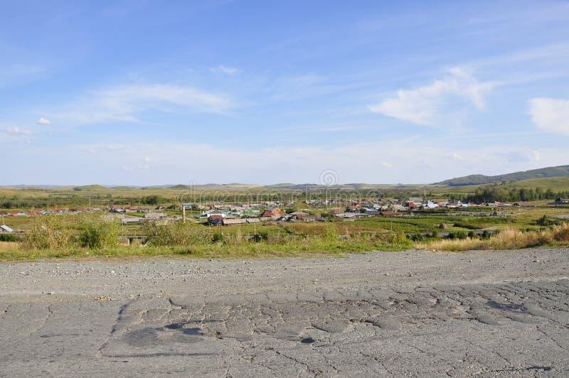 Nuages blancs dans le ciel bleu lumineux d'été au-dessus du village avec de petites maisons loin dans les montagnes et les domain image stock