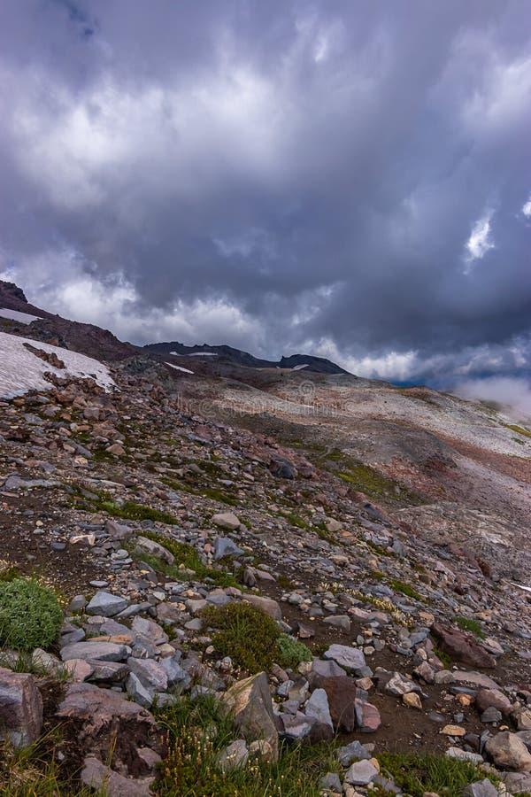 nuages blancs denses posés au-dessus du dessus de montagne rocheuse images stock