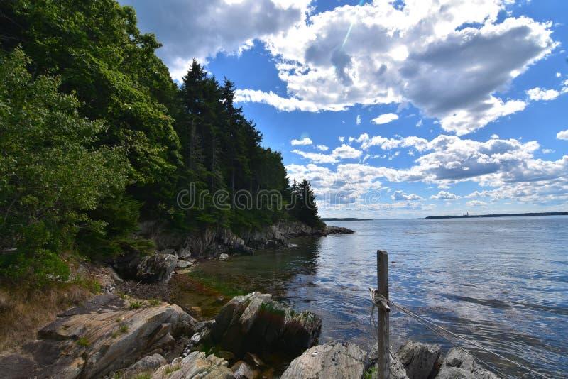 Nuages blancs pelucheux au-dessus de Rocky Maine Island Coast images libres de droits