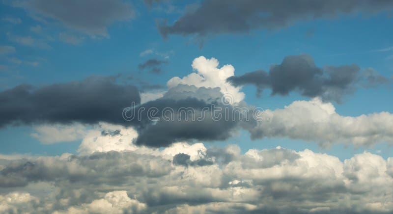 Nuages bouclés blancs mélangés aux nuages foncés contre le ciel bleu photos libres de droits