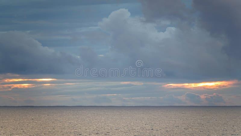 Nuages colorés au-dessus d'océan calme au coucher du soleil photo stock