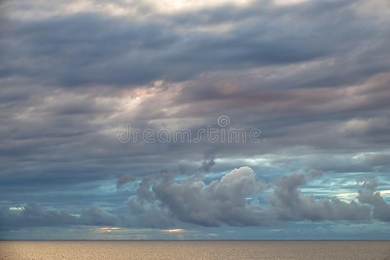 Nuages colorés au-dessus d'océan calme au coucher du soleil photographie stock
