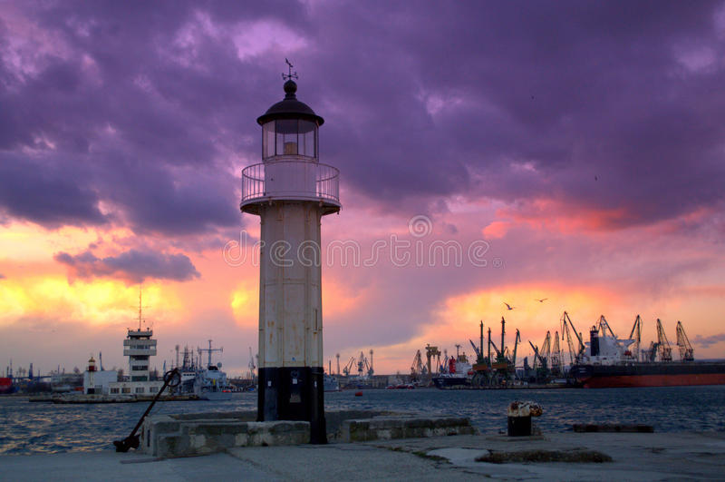 Nuages colorés au-dessus du port et du phare photographie stock